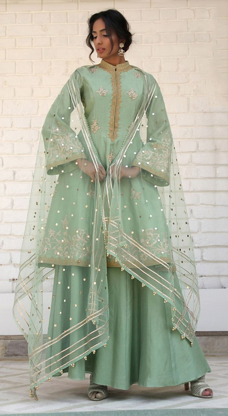 Rimple and Harpreet Narula. Pista green Chanderi silk A-line shirt featuring delicate gotta and tilla dori embroidery; paired with a soft tulle dupatta and silk sharara.