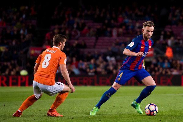 Ivan Rakitic of FC Barcelona conducts the ball past Goran Causic of CA Osasuna during the La Liga match between FC Barcelona and CA Osasuna at Camp Nou stadium on April 26, 2017 in Barcelona, Catalonia.