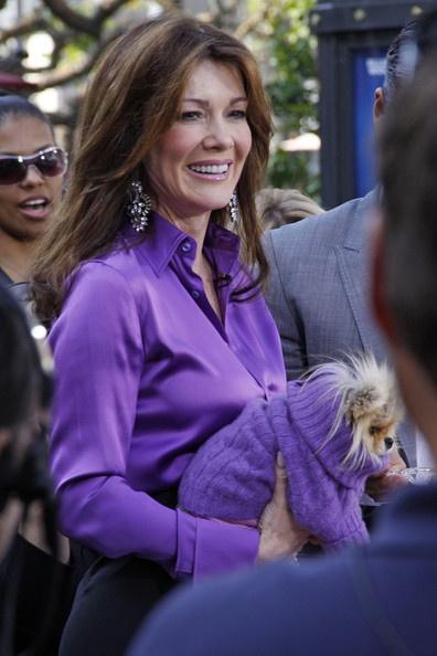 Lisa Vanderpump in purple blouse and black skirt with doggie in purple sweater