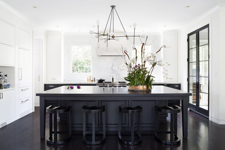 Luxurious black and white chic kitchen by Ella Scott Design. Come see the dramatic Before & After: Fussy Traditional to Urban Chic! #modernkitchen #blackandwhite #urbanchic #blackcabinets #sputnik #calacattamarble