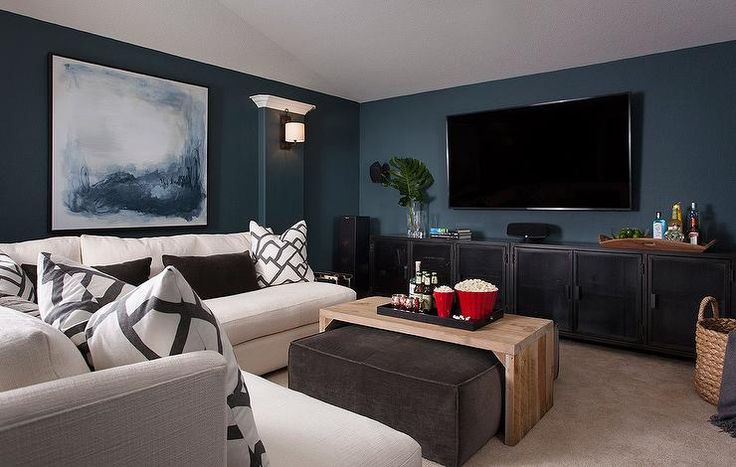 Chic family room features walls painted peacock blue lined with a blue abstract art piece placed over a white armless sectional lined with white and gray pillows in Zimba Charcoal Fabric as well as black lumbar pillows facing a gray velvet ottoman layered with a wood waterfall coffee table.