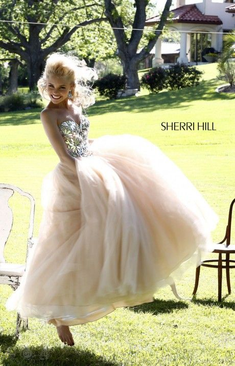 Embrace your inner flower child in this Sherri Hill 21307 ballgown!!! This dress features a strapless sweetheart neckline with a fitted bodice that comes together in a classic point at the center of the waist. The bodice is embellished with large flowers of sequins and beads hand sewn for perfection!!! A full layered tulle skirt completes this dress and makes this a must for prom!!!