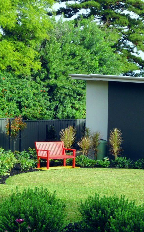 Colourful bench seat creates an inviting picture in the garden #gardenseat #perthlandscaping