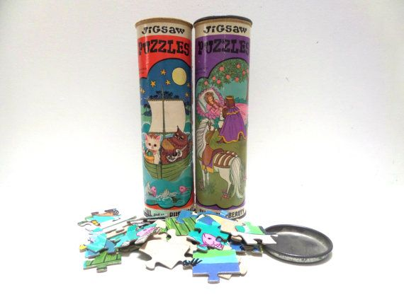 2 Vintage puzzles in tin cans with metal lids. Retro ilustrations on the containers are beautiful. Perfect to use as a decoration in a nursery