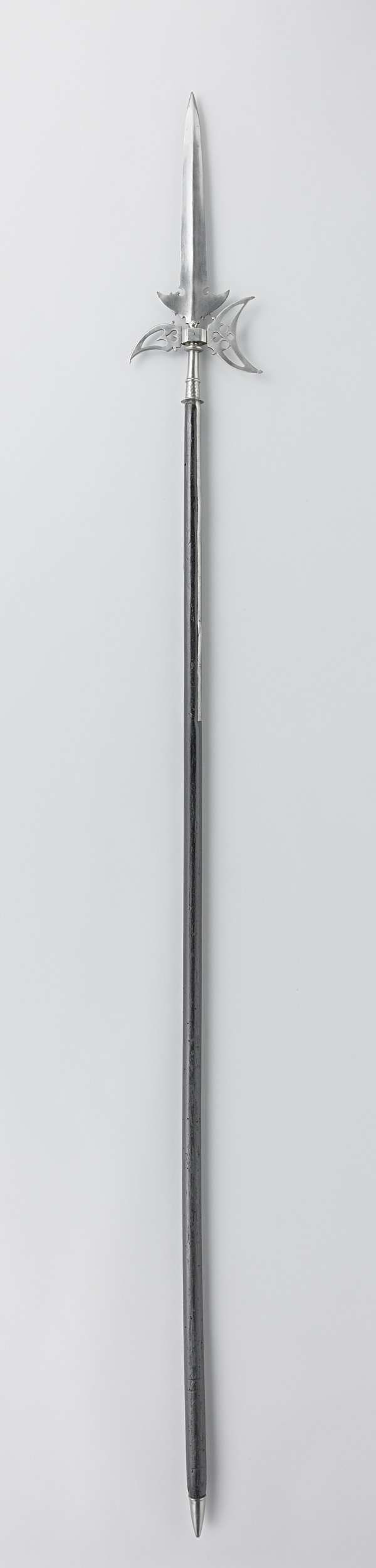 | Partizaan, c. 1600 - c. 1699 | Partizaan met gekartelde vleugels. Opengewerkte bijl met hart-vormige uitsparingen. Glad, zeshoekig middenstuk. Gladde schacht met ringornament. Twee lippen (51.0 cm). Aan het uiteinde van de stok een gladde, ijzeren punt. (7.0 cm)
