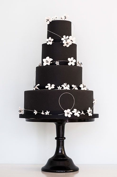 A dramatic black wedding cake looks chic when accented with white blooms. Courtesy of Rosalind Miller Cakes