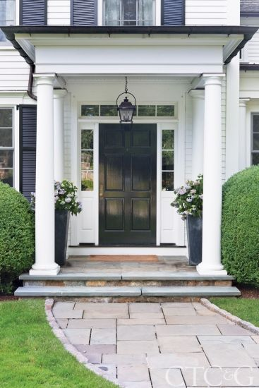 The home's traditional Colonial exterior is framed by a columned entry. #CTC&G
