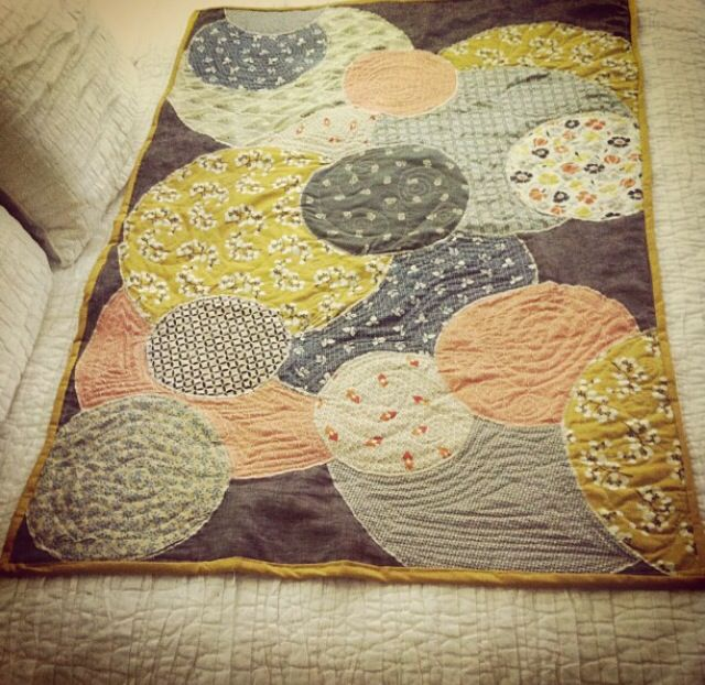 Crazy circles quilt. Blue. Orange. Yellow. Grey. Beige. Baby quilt for a girl. Florals. Polka dots. Linen and cotton top layer. Linen backing and binding. By White Hills Quilts.