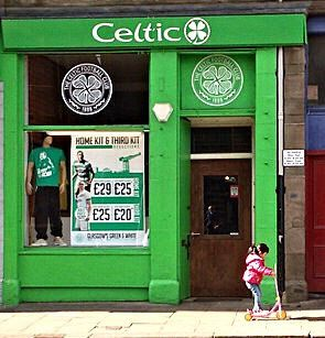Wee lassie scoots past the Celtic FC shop in Dundee