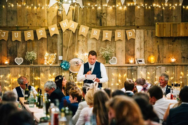 Rustic barn wedding in Devon, groom giving his speech in bunting clad barn wedding reception venue.  © Fairclough Photography