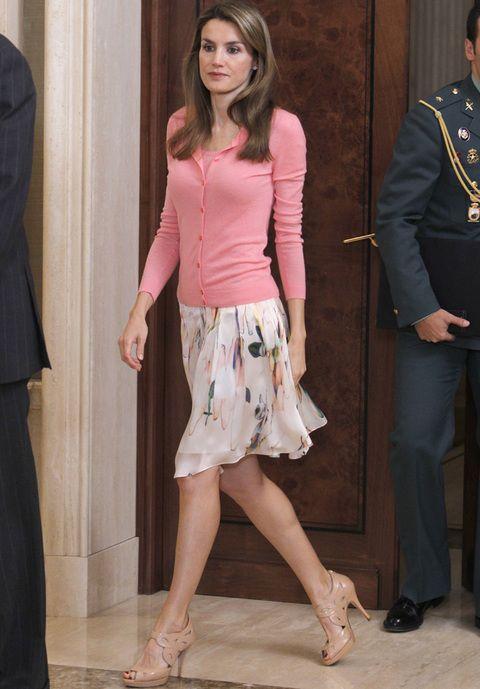 Fichamos este romántico look de Letizia con falda estampada en tonos pastel, rebeca rosa y una originales sandalias nude.