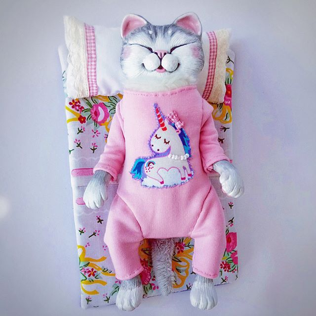 "Hello friends 😃 We are home and already working 😊 Mei Mei says "" Hi!"" I have finished her set just this morning. She has now cute pink pajamas with Unicorn print, blue Night-Star Bear (???) plush toy, cozy sleeping set along with adorable dress and flower headband 😉 She is a ""happy kitty sleepy, kitty purr purr purr 💤"" 😆😆😆 #catdoll #catart #catartist #cutedoll #artdoll #sleepykitty"