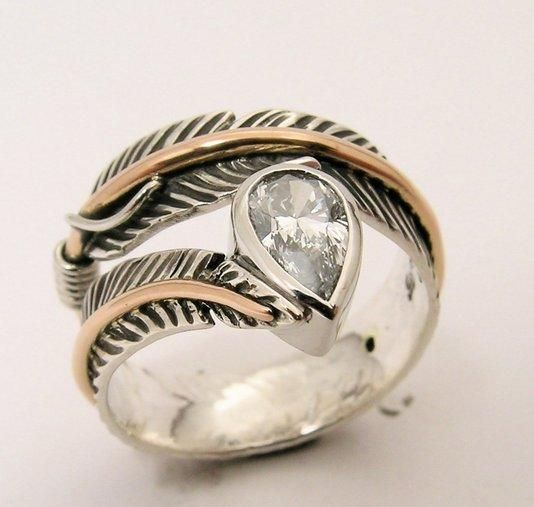Incredibly unique engagement ring for the bohemian bride - hand chased feathers holding a pear shaped diamond