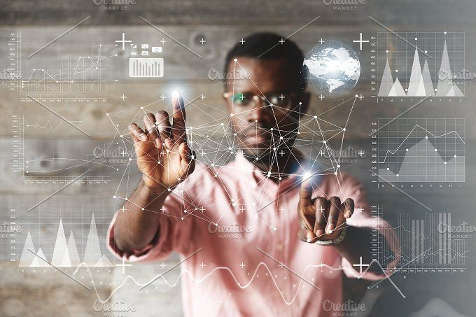 Double exposure. Black young businessman wearing glasses and casual shirt, touching futuristic screen interface with his fingers, making calculations, analyzing diagrams and schemes. Selective focus by WAYHOME studio on @creativemarket