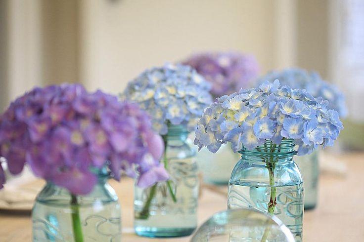 Tus centros de mesas con pequeños jarroncitos de cristal con hortensias.