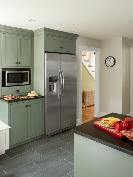 The refrigerator fits neatly in a niche that once held the hall coat closet, allowing more cabinet storage. | Photo: Eric Roth