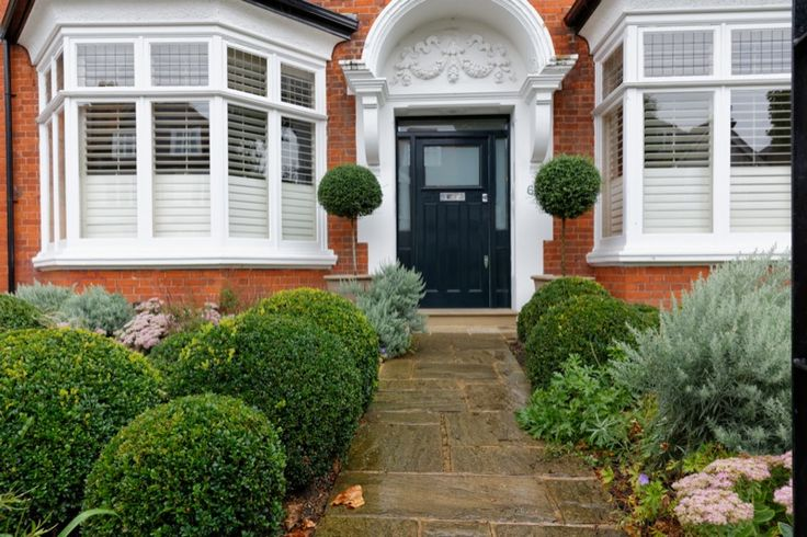 Smart red brick Victorian house with black front door and topiary