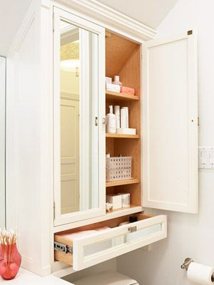 Storage cabinets above the toilet. Nice idea with the drawer.