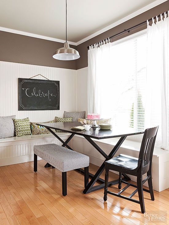 A large banquette creates lots of functional seating in this kitchen. The wraparound banquette matches the beadboard wall and easily flows with the rest of the space. An easy-to-make DIY chalkboard gives personality to the nook and a padded striped bench provides seating acrosss from the window.
