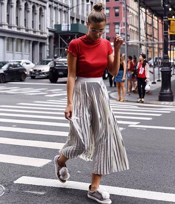 street style, t-shirt vermelha, saia mídi plissada prateada, tênis com pompom, coque alto