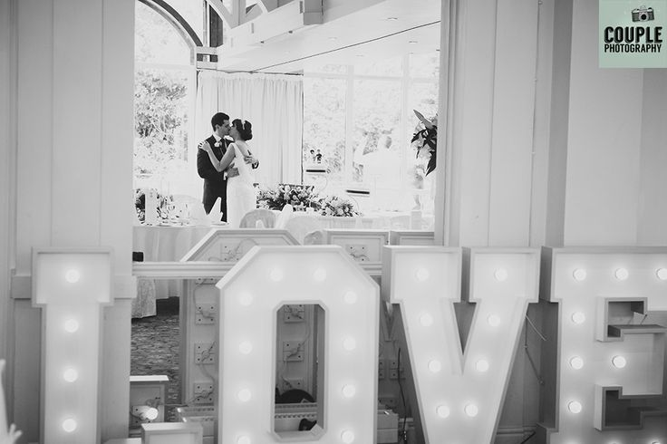 Light up letters spell out LOVE as the bride & groom steal a kiss. Weddings at The Keadeen Hotel Photographed by Couple Photography.