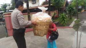 Kanit Sabhara Polsek Grati Menolong Warga yang Kelelahan Membawa Barang Jualannya