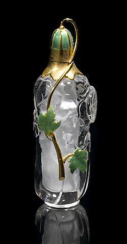 Cristal de roca, oro y esmaltada Botella Perfume De Manfred Wild Idar-Oberstein, Alemania Tallada en una sola pieza de cuarzo transparente de cristal de roca, la botella de perfume ha aplicado decoraciones de oro amarillo de 18K con la decoración de esmalte verde en forma de hojas de hiedra. La tapa extraíble posee una cantidad sustancial de oro, también, y tiene la decoración de esmalte. Sellada con el monograma OHG y 750. Altura 5 en