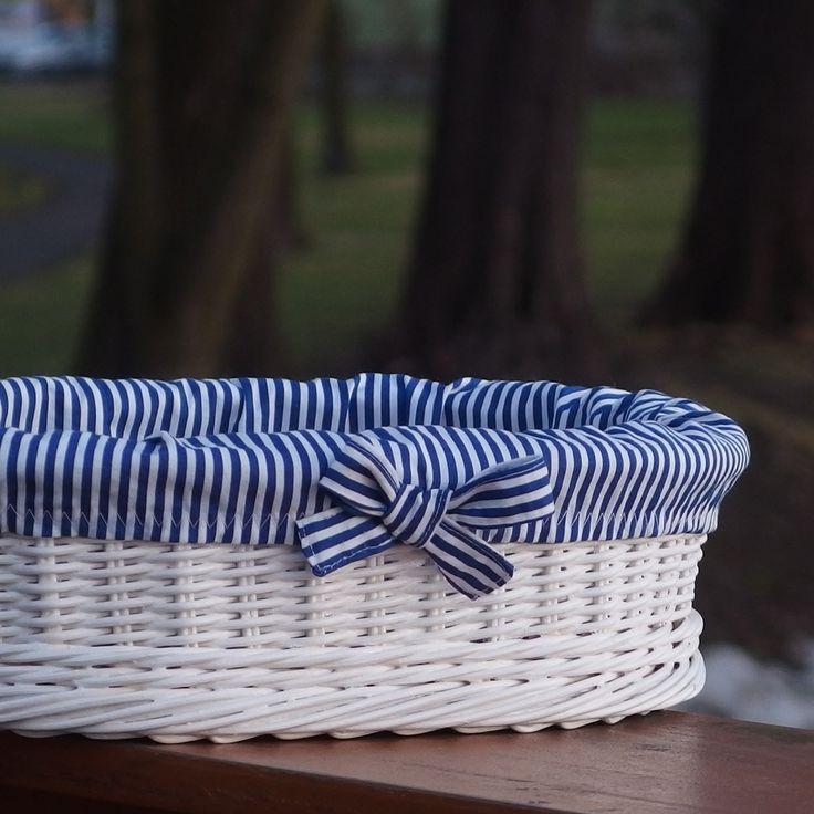 Bílý koš s vůní dálek Koš je upleten z přírodního pedigu, dno je z 8 mm překližky a celý je natřen bílou barvou vhodnou na dětské hračky a styk s potravinami. Košilka je ušita z modrobílé 100% bavlny. Vpředu koše je mašle. rozměry 30x25x8 cm