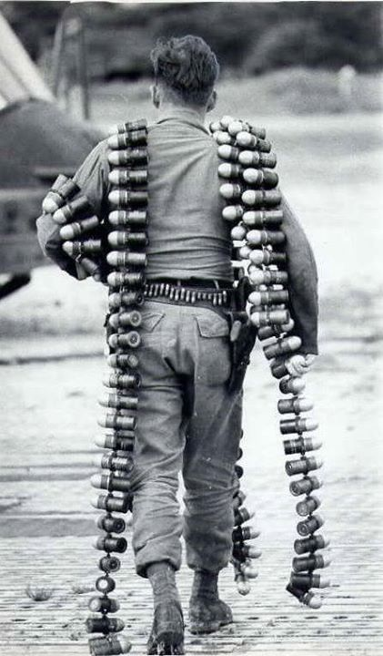 UH-1 crew chief heading toward his bird to load up the linked 40mm grenades he is carrying. Armed with a .45 holstered with spare ammo carried in the loops on his belt [446 761] 1967 Bien Hoa South Viet Nam