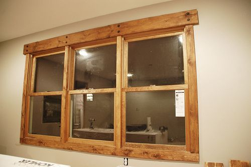 Rustic window trim with hand beveled pine boards, squared ends, honey tone stain and black lag screws