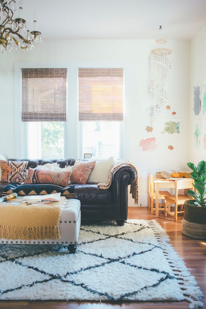 Eclectic, bohemian living room with printed rug over hardwood floors, a plush leather couch, white walls and a tufted ottoman | Thoughts from Alice