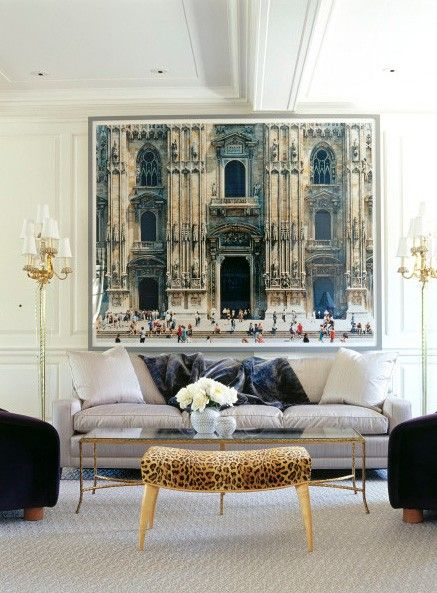 This space is amazing. I love the huge photo, the molding, the lamps, the coffee table, the velvet couch, the furry throws, and that awesome leopard stool.