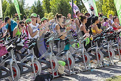 Group of men and women cheering after successfully finishing their exhausting cardio exercise during a public cycling marathon on stationary bikes on 15.09.2013 in Bucharest, Romania.