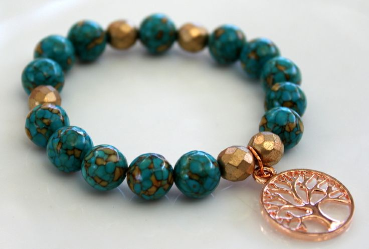 """Contemporary Bracelet B091  $25 This bracelet is made up of Blue Turquoise (stabilised) Gemstone Beads and Czech Fire Polished Glass Beads in light Gold. I added a Rose Gold Plated """"Tree of Life"""" Charm in the centre.  Easy to get on and off, this is a great piece to wear alone or stacked with other bracelets in your wardrobe. Made with two layers of sturdy elastic cord, the bracelet will comfortably fit an average size wrist.  Length – 19cm"""