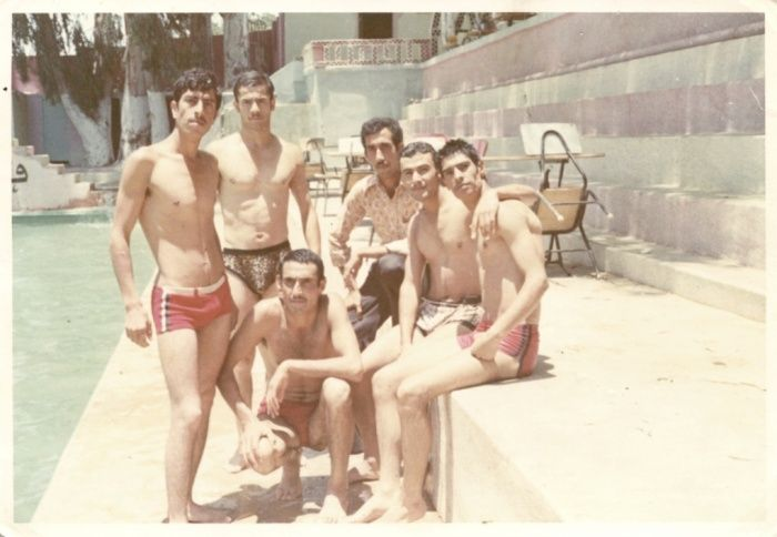 Young Lebanese men standing by a pool in the 70s