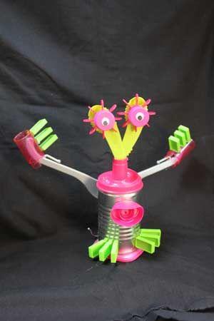 Robot gemaakt van blikje, kledinghanger, dopjes en deksels