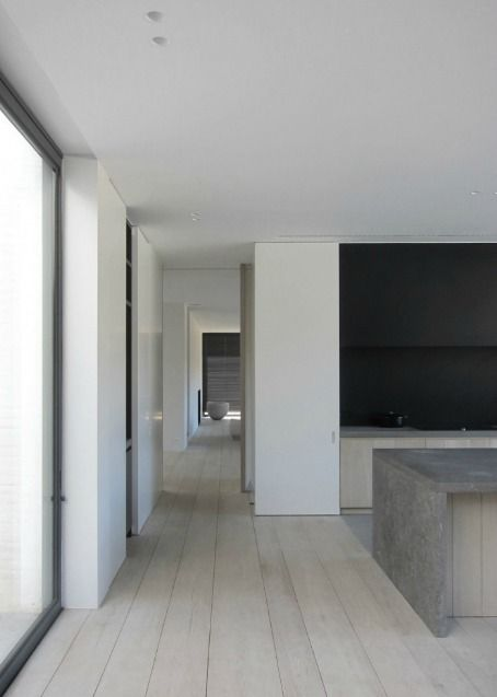 Oak wooden floors + kitchen island in Belgian blue stone. V-T Residence by Vincent Van Duysen