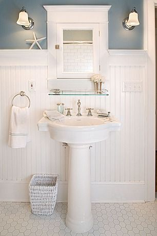 White wainscoting with a wide baseboard, twin sconces and a glass shelf over the pedestal sink in a bathroom.