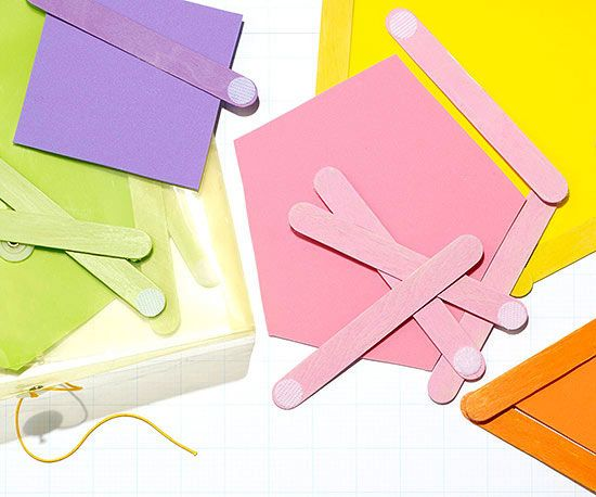 Teach your toddler colors, shapes, and matching by cutting out colorful paper and painting ice-pop sticks in the same hue so they can frame the papers.