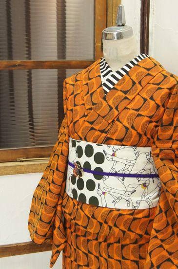 オレンジと黒のバイカラーで織り出された波ストライプがモダンなウールの単着物です。