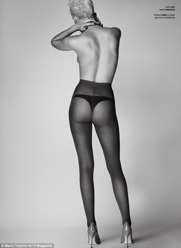 Camera shy: In one of the images from the shoot, Kristen is topless and wearing only a thong, sheer tights, and heels