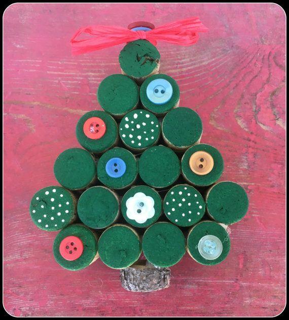 Abbellire la vostra casa con questo albero di Natale di sughero del vino! Questo elemento a mano dotato di tappi per vino, pulsanti, colori acrilici e un po  di ramo di albero. Sarà laggiunta perfetta per le vostre decorazioni di Natale.  Ogni albero è dipinta a mano e poi decorato con bottoni. Colore e pulsanti varierà.  Le dimensioni sono H: 5 1/2 in W: 4 1/2 D: 1 1/2