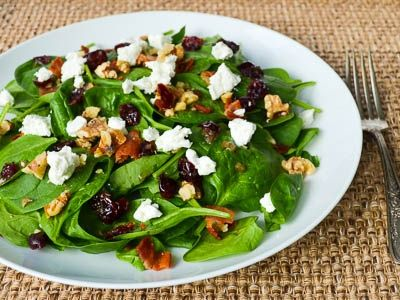 Spinach Salad with Warm Bacon Dressing is great for a fall day. Spinach is in season and the warm dressing is nice in the cooler weather. Bacon, cranberries, walnuts, and goat cheese not only go well with the spinach, they also make for a pretty and colorful salad. A green background is dotted with red, white, and a touch of earthy brown. It is a feast for the eyes and the stomach. Serve it with warm french bread and a glass of wine.