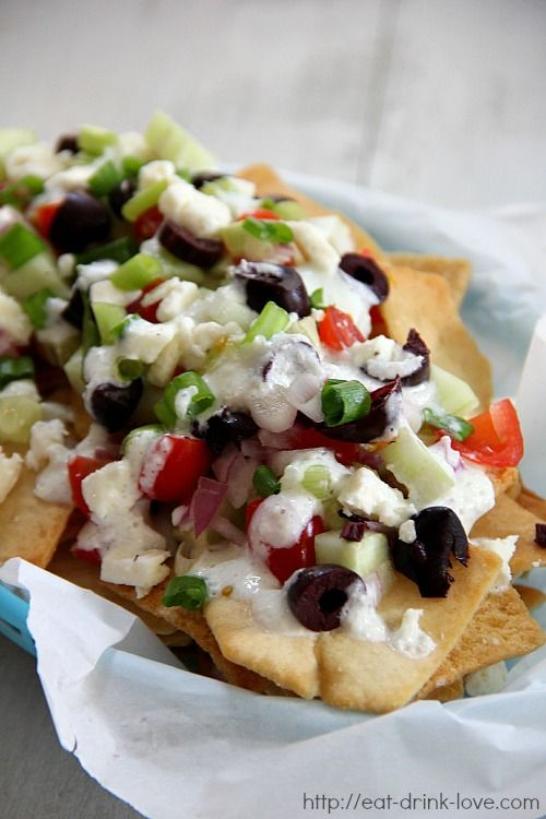 Greek Nachos - crispy pita chips topped with fresh cucumber, onions, tomatoes, kalamata olives, feta cheese, and tzatzkiki