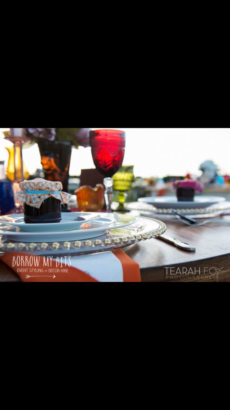 A twist to the use of the gold beaded charger in a shabby chic boho setting.... Depression glass and mismatched wine glass goblets match in perfectly!!! Bright and bold wedding setting...