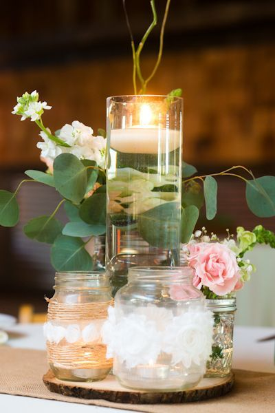 Single floating candle surrounded by mason jars wrapped in twine and lace - rustic centerpiece