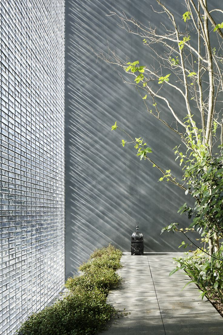 A Tree Filled Courtyard Is Glimpsed Through The Shimmering Glass Brick  Facade Of This House In Hiroshima, Designed By Japanese Architect Hiroshi  Nakamura