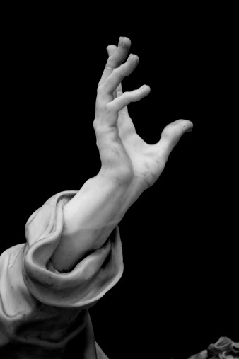 'Hand'   Detail of the Statue of Saint Peter, one of the sculptures of the Twelve Apostles inside the Basilica of St. John Lateran. Rome, Italy. Sculpture by Pierre-Étienne Monnot (1657, Orchamps-Vennes - 1733, Roma), 'San Pietro', 1708-13. Black and white, grained and vignetted image.