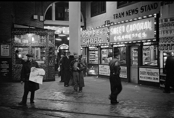 The tram news stand and coffee shop illuminated at night in the BC Electric Building at 425 Carrall St. City of Vancouver Archives, AM640:CVA 260-778, 1937 - Photographer James Crookall | Megaphone - Vancouver's Street Paper