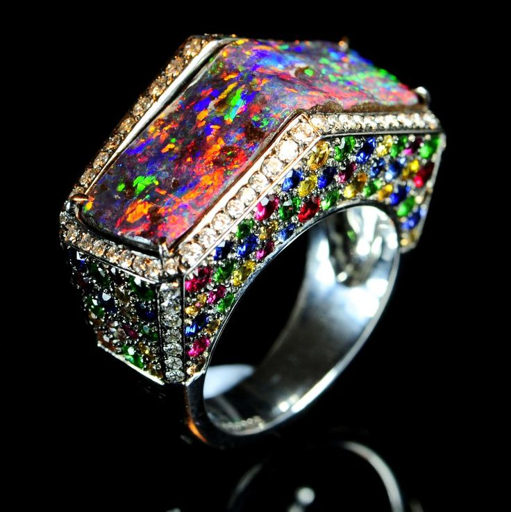 This ring was created by a famous old Paris designer 'Marchak'. It is called Rialto and was inspired by the Venetian Rialto bridge. What beautiful use of the faceted stones highlighting the rich colors within the stunning boulder opal.